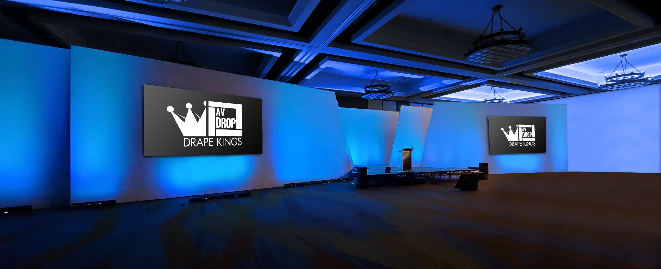 Angled Modular Backdrop with two front projection screens and blue up lighting on white walls for corporate meeting
